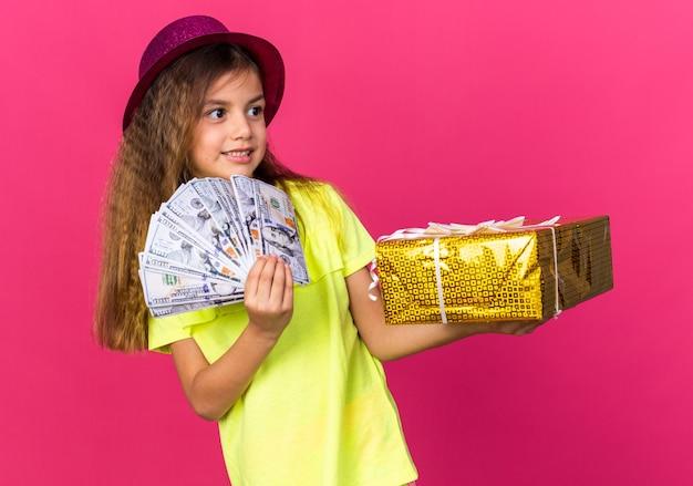 Erfreutes kleines kaukasisches mädchen mit lila partyhut, das geschenkbox und geld hält, die seite lokalisiert auf rosa wand mit kopienraum betrachten