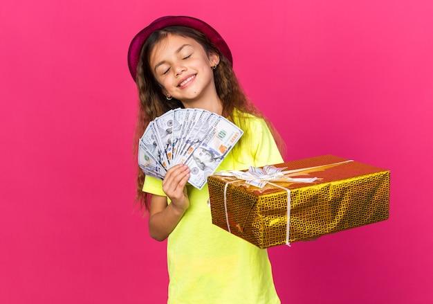 Erfreutes kleines kaukasisches mädchen mit lila partyhut, der geschenkbox und geld lokalisiert auf rosa wand mit kopienraum hält