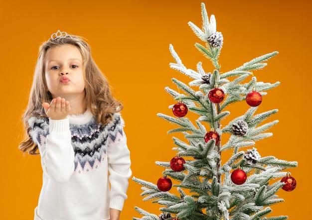 Erfreutes kleines mädchen, das nahe weihnachtsbaum steht und tiara mit girlande am hals trägt, zeigt kussgeste lokalisiert auf orange hintergrund