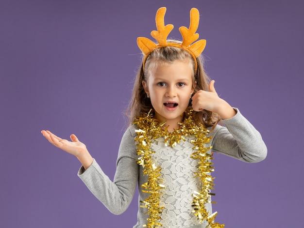 Erfreutes kleines mädchen, das weihnachtshaarbügel mit girlande am hals trägt, die telefonanrufgeste und punkte seitlich lokalisiert auf blauem hintergrund mit kopienraum zeigt