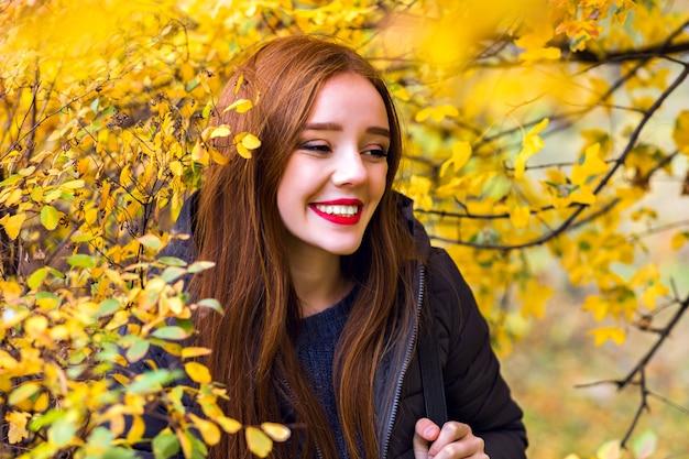 Erfreutes langhaariges mädchen, das spaß im park mit gelbem laub hat. außenporträt des lachenden brünetten weiblichen modells, das weg schaut, während es im wald aufwirft.