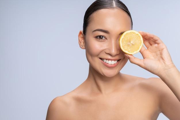 Erfreutes mädchen, das ein lächeln auf dem gesicht behält und zitrusfrüchte in der kosmetik verwendet