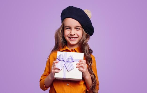 Erfreutes mädchen im hut, das geschenkbox zeigt