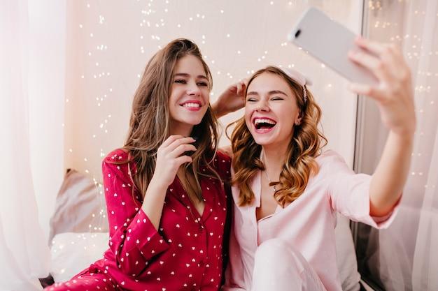 Erfreutes mädchen im rosa pyjama, das spaß in ihrem zimmer mit bester freundin hat. fröhliche junge dame, die am morgen mit schwester selfie macht.