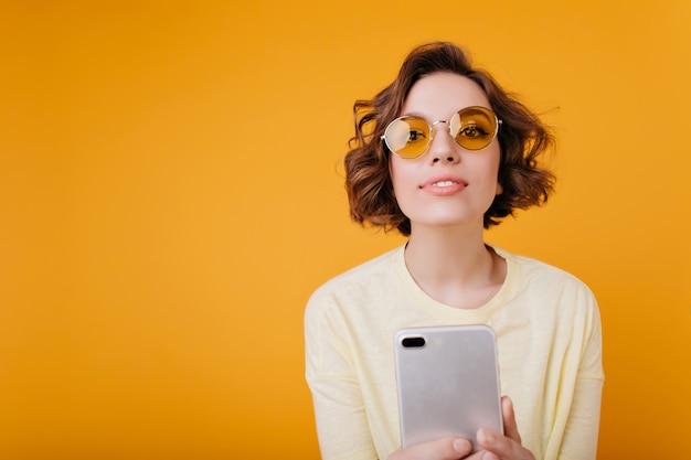 Erfreutes mädchen mit gewellter frisur, die selfie auf orange raum macht