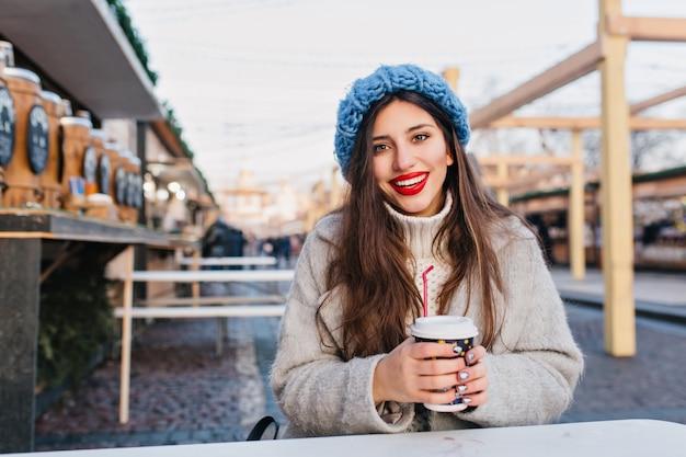 Erfreutes mädchen mit langen dunklen haaren, die auf der straße lächeln, während kaffee trinken. nette junge frau im mantel und im pullover, die mit tasse tee am kalten tag auf stadt aufwirft.