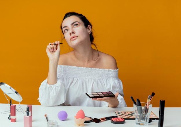 Erfreutes schönes mädchen sitzt am tisch mit make-up-werkzeugen, die lidschattenpalette und make-up-pinsel lokalisiert auf orange wand halten