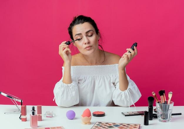 Erfreutes schönes mädchen sitzt am tisch mit make-up-werkzeugen, die wimperntusche mit geschlossenen augen lokalisiert auf rosa wand anwenden