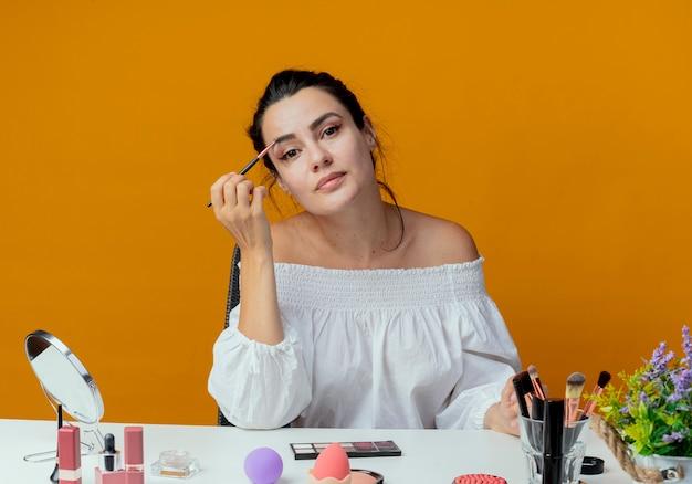 Erfreutes schönes mädchen sitzt am tisch mit make-up-werkzeugen hält make-up-pinsel, der isoliert auf orange wand schaut