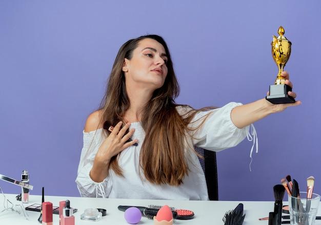Erfreutes schönes mädchen sitzt am tisch mit make-up-werkzeugen hält make-up-pinsel und schaut auf gewinner tasse isoliert auf lila wand