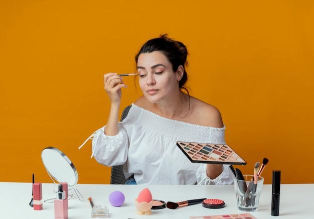 Erfreutes schönes mädchen sitzt am tisch mit make-up-werkzeugen schaut auf spiegel, der lidschatten mit make-up-pinsel auf orange wand isoliert anwendet