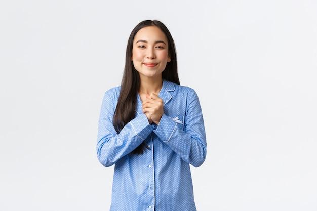 Erfreutes und entzücktes asiatisches mädchen im blauen pyjama, das hände zusammen hält