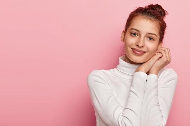 Erfreutes weibliches model neigt den kopf und lächelt sanft, hält die handflächen in der nähe des gesichts zusammengedrückt, hat kein make-up, trägt einen weißen rollkragenpullover, schaut mit blauen augen direkt in die kamera, isoliert über rosa hintergrund