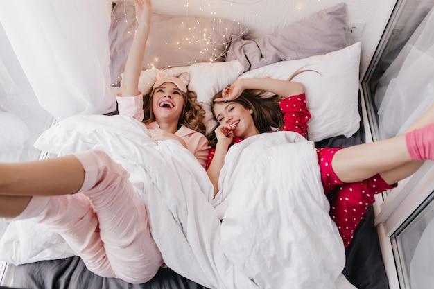 Erfreutes weibliches modell, das unter weißer decke liegt und lacht. innenaufnahme von zwei fröhlichen mädchen, die wochenendmorgen im bett verbringen.
