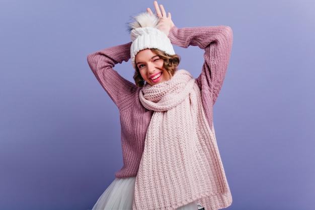 Erfreutes weibliches modell mit glücklichem gesichtsausdruck, der in winterkleidung aufwirft und lächelt. kurzhaarige frau im schal, die positive gefühle auf lila wand ausdrückt.