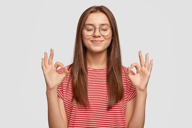 Erfreutes zufriedenes junges weibliches model macht keine geste, trägt transparente brille, hat langes dunkles haar