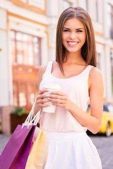 Erfrischen sie sich nach dem shopping-tag. schöne junge lächelnde frau, die einkaufstüten und eine tasse heißes getränk hält, während sie im freien steht