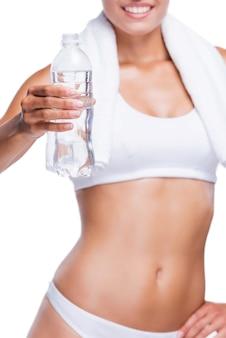 Erfrischen sie sich! nahaufnahme einer schönen jungen frau in weißem bh und höschen, die eine flasche mit wasser hält, während sie isoliert auf weiß steht