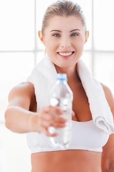 Erfrischen sie sich! schöne reife frau in sportkleidung, die eine flasche mit wasser ausstreckt und lächelt