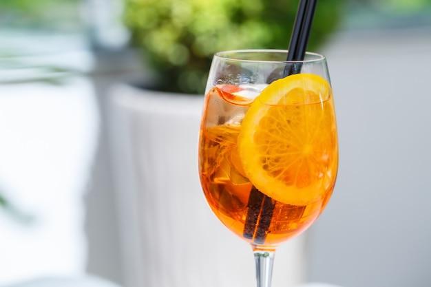 Erfrischend leichter köstlicher sommer-aperol-cocktail mit eis und orange im glasbecher, erfrischungsgetränk mit strohhalmen für mädchen
