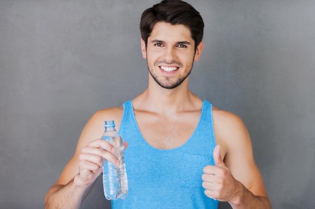 Erfrischend nach dem training. fröhlicher junger muskulöser mann, der eine flasche mit wasser und daumen hoch hält, während er vor grauem hintergrund steht