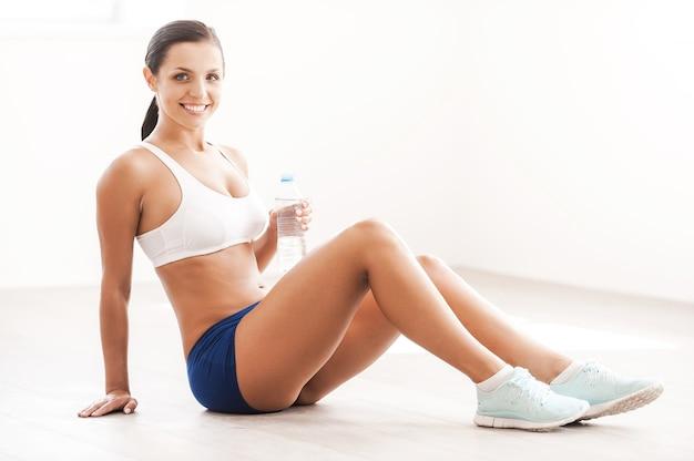 Erfrischend nach dem training. schöne junge lächelnde frau in sportkleidung, die auf dem boden sitzt und eine flasche mit wasser durchlöchert