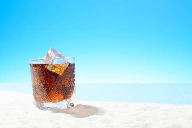 Erfrischende cola mit eis im glas an der sandküste