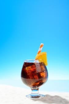 Erfrischende cola mit eis und einer orangenscheibe im glas an der sandküste