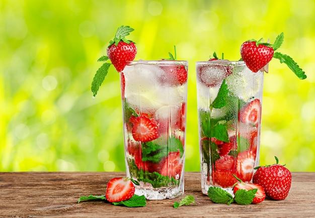 Erfrischende limonade mit minze und erdbeeren auf unscharfem sommerhintergrund. speicherplatz kopieren