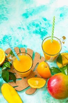 Erfrischende sommer-mango und frisch gepresster saft von zitrusfrüchten konzept der vegetarischen küche