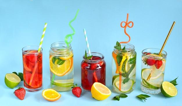 Erfrischende sommergetränke aus zitrone, limette, erdbeere, orange, minze auf blauer oberfläche. entgiftung, gesunde ernährung, fitnessgetränke. reisekonzept. kopierraum.