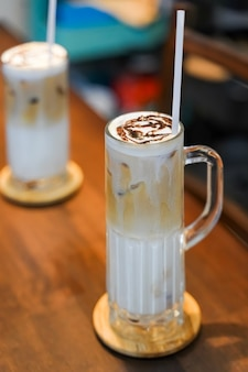 Erfrischende sommergetränke bestehen aus drei schichten: kalte milch, kaffee und kalte schaummilch in einem hohen glas.