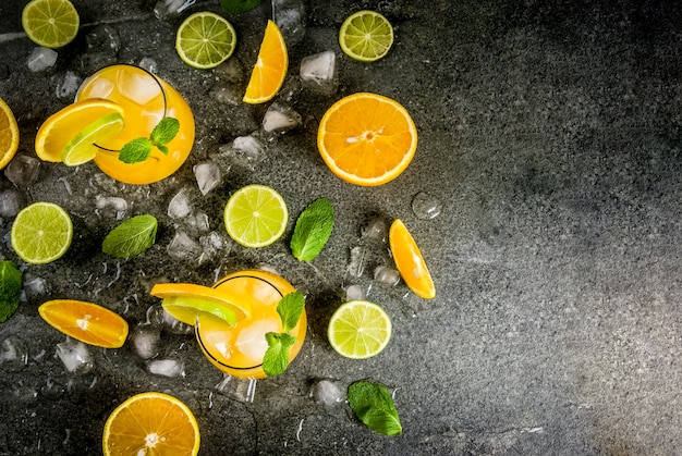 Erfrischende sommergetränke mit vitaminen. zitruspunsch mit orangen und limette, mit minzezweigen, mit eis gekühlt. auf schwarzem steintisch, mit zutaten,