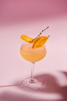 Erfrischender alkoholcocktail mit orangefarbenem tropischem rosa