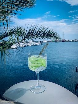 Erfrischender cocktail mit limette mit dem meer