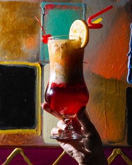 Erfrischender cocktail mit zitronenscheibe und kirsche