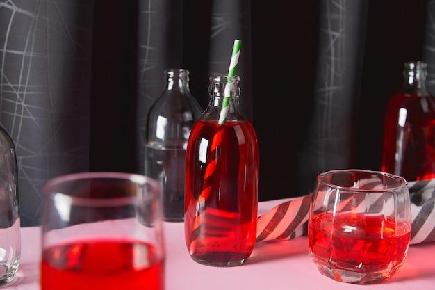 Erfrischender cranberry-limonade-cocktail in flaschen mit palmblatt auf rosafarbenem tisch. sommergetränk im minimalistischen stil.