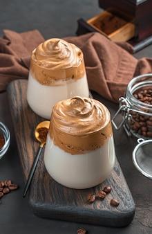 Erfrischender dalgona-kaffee in zwei klaren gläsern an einer braunen wand. seitenansicht, vertikal.
