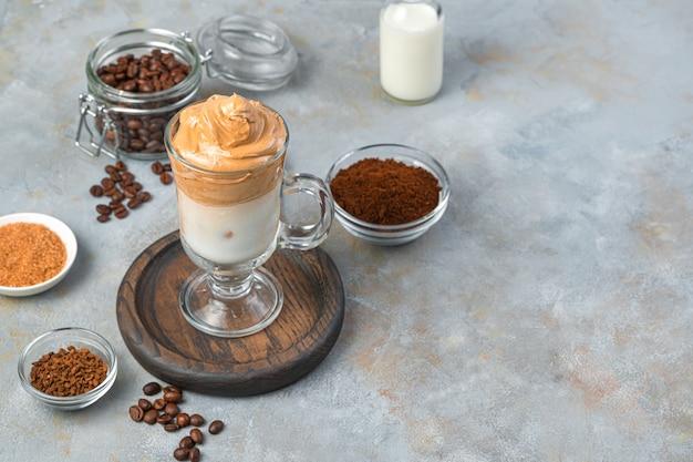 Erfrischender dalgona-kaffee mit milch, schaum und eis an einer grauen wand. koreanisches kaffeegetränk.