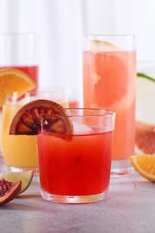 Erfrischender frisch gepresster sizilianischer orangensaft unter frischen detox-zitrussäften aus orange, grapefruit, limette