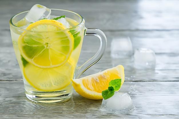 Erfrischender kalter grüner tee mit zitrone auf holzoberfläche