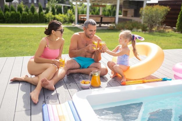 Erfrischender kalter saft. große glückliche familie, die beim sonnenbaden in der nähe des pools erfrischenden kalten saft trinkt?