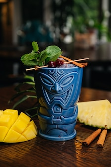 Erfrischender kalter tiki drink cocktail mit ananas-mango-minze und zimt