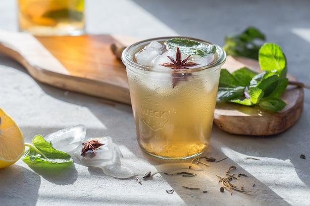 Erfrischender kombucha-eistee oder apfelwein in glas mit etikettiertem kombucha. gesundes natürliches getränk mit probiotischem geschmack. speicherplatz kopieren.