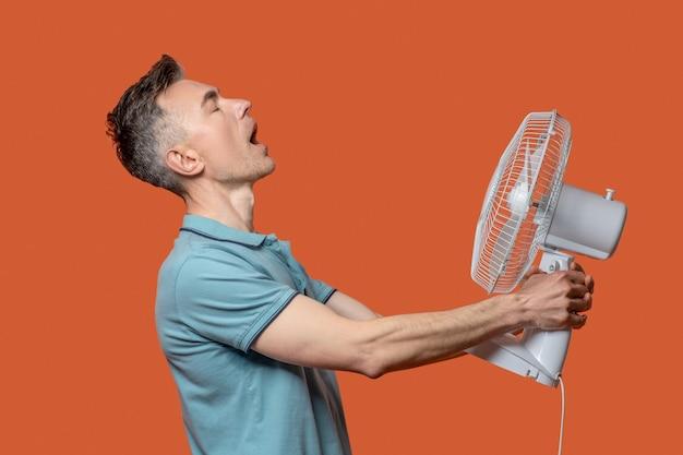 Erfrischender luftstrom. profil eines mannes mit geschlossenen augen und offenem mund, der einen ventilator in den händen hält und den luftstrom auf sich selbst richtet