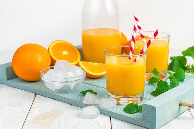 Erfrischender orangensaft mit minze und eiswürfeln auf einem hellblauen brett auf einem hellen schreibtisch.