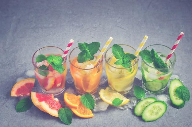 Erfrischender sommer trinkt wasser mit eis und zitrone, orange, traube