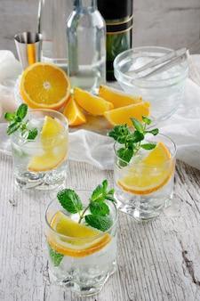 Erfrischender sommercocktail mit weißem portwein, gemischt mit trockenem oder süßem wein mit ein paar tropfen orange und einem hauch minze.