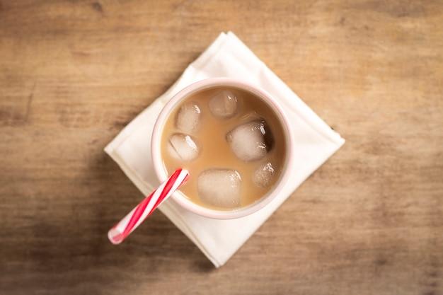 Erfrischender und belebender eiskaffee in einem glas auf einem holztisch. konzept coffeeshop, durst stillen, sommer. flache lage, draufsicht