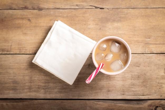 Erfrischender und verspannender eiskaffee in einem glas auf einem hölzernen hintergrund. konzept coffeeshop, durst stillen, sommer. flache lage, draufsicht